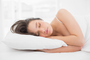 Pretty young woman sleeping in bed