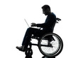 handicapped man computing laptop computer  in wheelchair silhoue