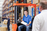 Supervisor nearing worker in forklift in distribution warehouse
