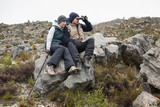 Couple sitting on rock with binoculars while on a hike