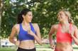 Two friendly pretty women running in a park