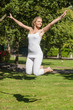 Cheerful young woman jumping in a park