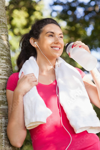 Cheerful young woman drinking water and leaning against a tree
