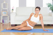 Young sporty woman posing sitting on an exercise mat