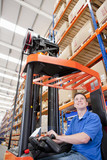 Smiling worker operating forklift in distribution warehouse
