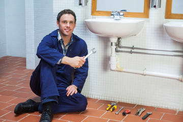 Handsome smiling plumber sitting next to sink holding wrench