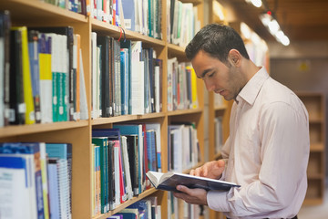 Intellectual man reading a book standing in library