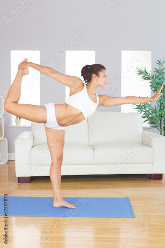 Concentrated slim woman stretching her body in yoga pose