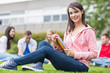 Smiling college student with blurred friends sitting in park