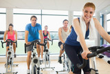 Happy woman teaches spinning class to four people