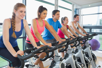 Five people working out at spinning class