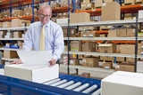 Supervisor examining paperwork and boxes on production line in distribution warehouse