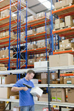 Worker scanning box  among shelves in distribution warehouse