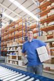 Portrait of smiling worker holding scanner and boxes at production line in distribution warehouse