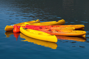 Bright yellow and red canoes moored with buoy