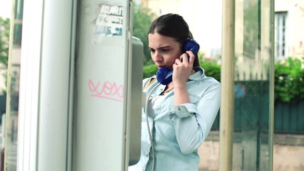 Worried woman try to make call in broken telephone booth