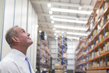 Smiling supervisor looking up at shelves in distribution warehouse