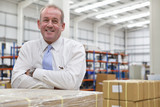 Portrait of smiling supervisor with arms crossed in distribution warehouse