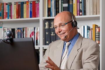 Froehlicher Mann telefoniert ueber das Internet