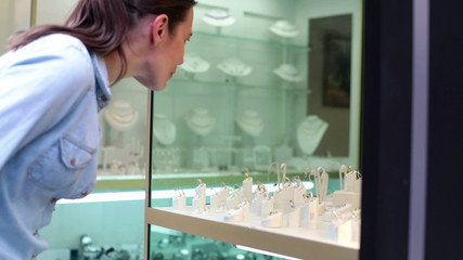 Woman looking at beautiful jewellery on shopwindow