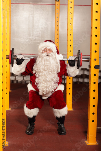Santa Claus  lifting weights in gym -  training before Christmas