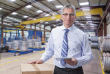 Portrait of smiling supervisor holding digital tablet in warehouse