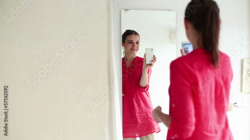 Woman taking photo of herself with cellphone in front of mirror