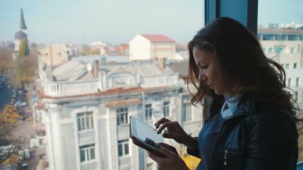 girl tourist near a window with tablet computer