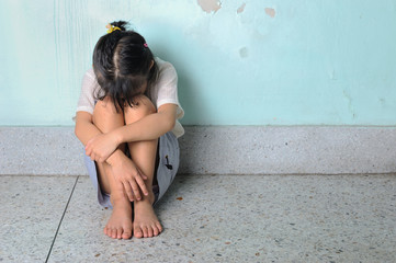 sad and depressed little girl sitting near the wall