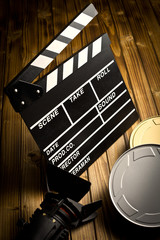 clapper board with movie light and film reels