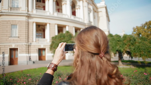 Beautiful, young girl tourist takes pictures on the smartphone