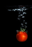 Fresh tomato dropped into water