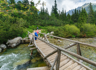 Stream and family on wooden bridge (High Tatras, Slovakia) .