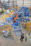 Businessman and worker controlling robotic machinery lifting steel fencing on production line in manufacturing plant