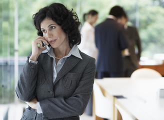 Businesswoman talking on phone, colleagues in background