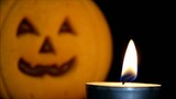 Candle burns in front of Halloween pumpkin