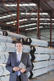 Portrait of smiling businessman with digital tablet in front of steel tubing in warehouse