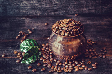 Coffee grains with green leaves in a copper pot