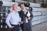 Bank manager and businessman with digital tablet talking in front of steel tubing in warehouse