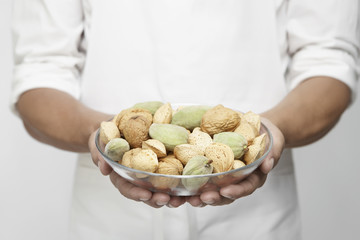 Chef holding bowl of nuts (mid section)