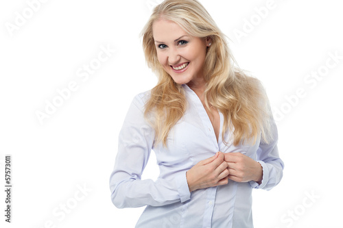 Young woman buttoning shirt
