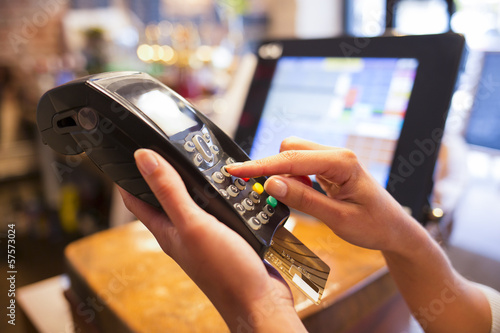 Leinwandbild Motiv Woman hand with credit card swipe through terminal for sale