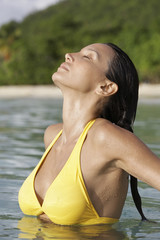 Young woman standing deep in water with eyes closed