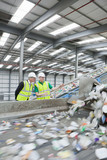 Businessman and worker watching plastic on conveyor belt in recycling plant