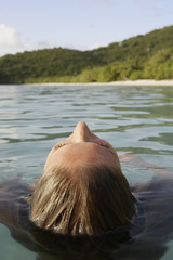 Mid adult woman swimming in ocean (rear view), St. John, US Virgin Islands, USA