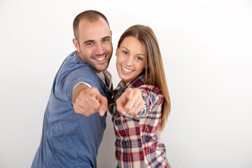 Trendy couple on white background pointing at camera