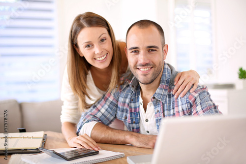 Young cheerful couple calculating savings for home investment