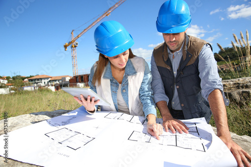Construction people looking at blueprint