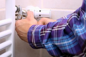 Mann repariert Flachheizkörper mit Rohrzange,
