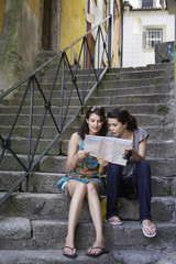 Two young women reading road map on steps